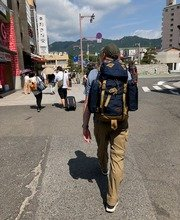 Collin Asmus walking down a street away from the camera with a large back pack on and mountains in the distance