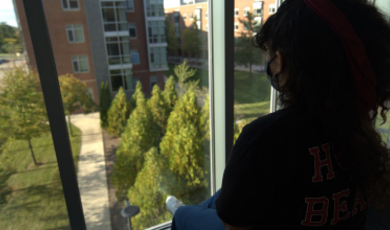 A student sits and looks out window on campus