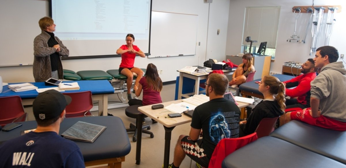 A class with desks and padded tables. At the front of the class a student sits on a padded table with her hands clasped together. The professor is standing next to the table with her hands similarly clasped.  Another student is holding the first student's ankle.