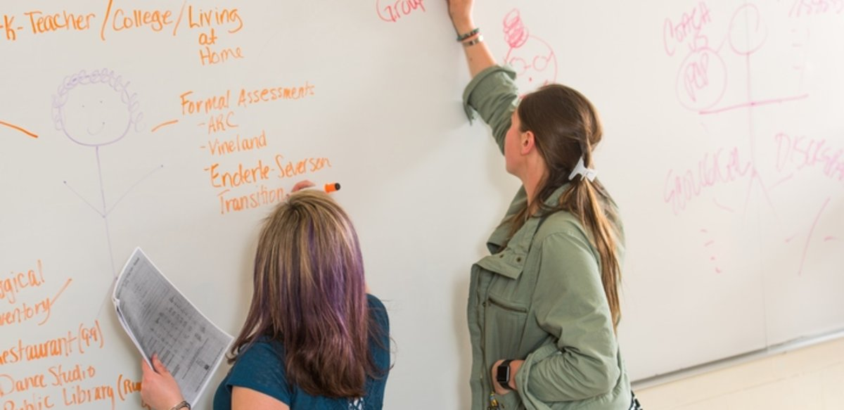 "Two students writing with markers on a white board. Words on the board include ""Formal Assessment"" and ""Coach vs. PCP."""