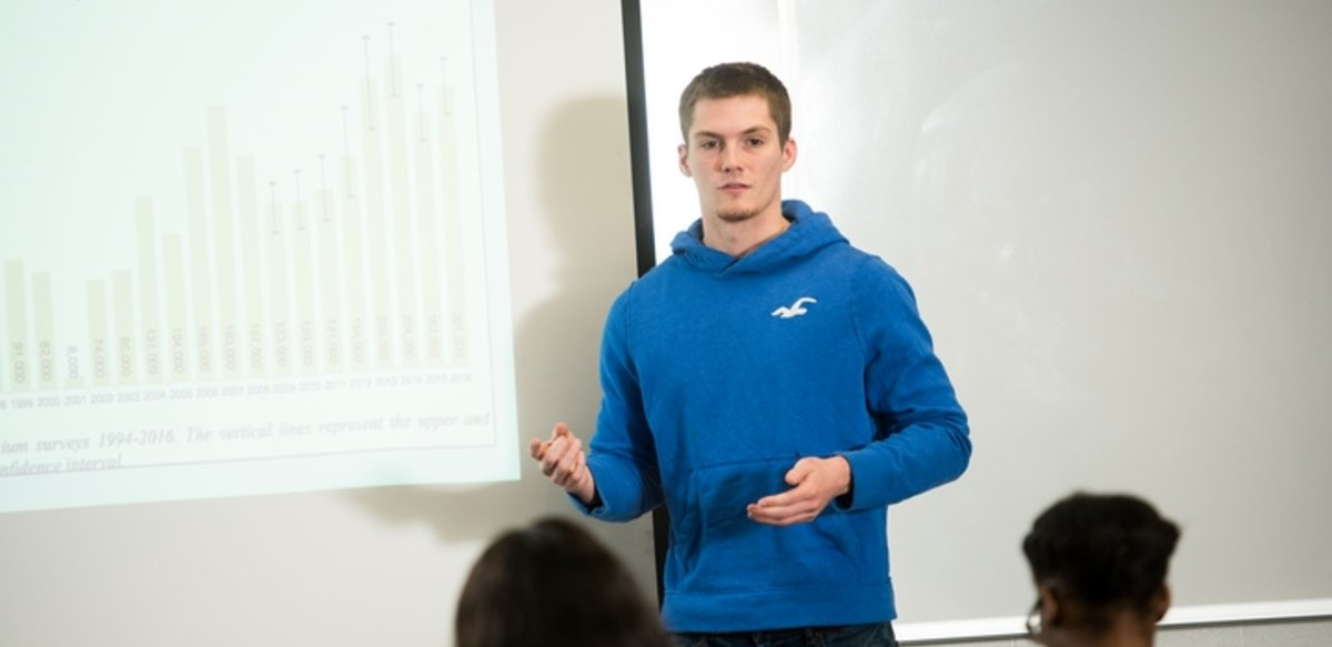 A student giving a presentation at projection screen in class