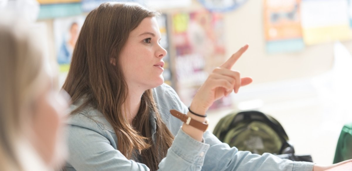student in class speaking and pointing