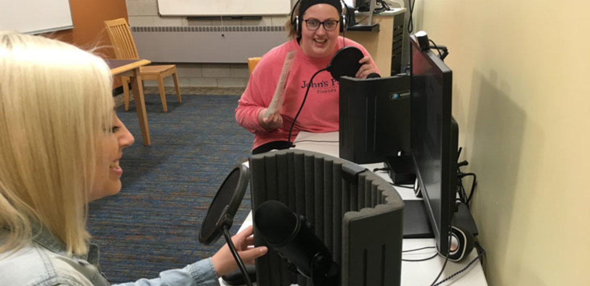 Two students laugh as they work together to record audio in the podcast studio.