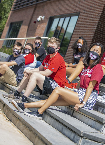 Masked students gathered on some steps